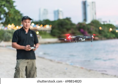 CHONBURI,THAILAND - August 12, 2017: DJI Mavic Pro drone with drone operator on Pattaya beach using remote controller controlling flight for photography and recreation