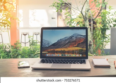 CHONBURI,THAILAND - NOV 12,2017 : Office table with Macbook Pro retina 13 inch with macOS High Sierra Screen, Apple iphone6, Blank screen notebook paper on Garden tree.