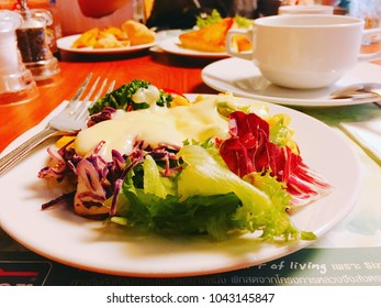Chonburi,Thailand-February 10, 2018.Vegetable salad with sauce on white plate at Sizzler restaurant.Sizzler is West restaurant from United states,lot of franchise in Thailand.Photo with Thai alphabet
