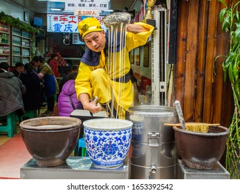 Chongqing, China - January 3, 2020 : Seller in Ancient Suit show how to make noodle at Chongqing ancient market
