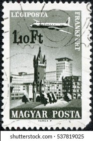 CHONGQING, CHINA - May 10, 2014:A stamp printed in Hungary shows plane abowe Frankfurt am Main, aircraft, Eschenheimer Turm and Eschenheimer Gate, circa 1966