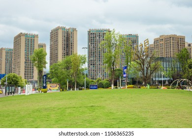 Chongqing, China – May 17, 2018: Parks in urban centers, green grasslands and high-rise buildings