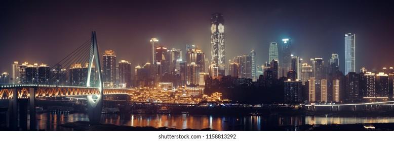 Chongqing skyline with urban buildings, bridge and Hongyadong shopping complex at night.