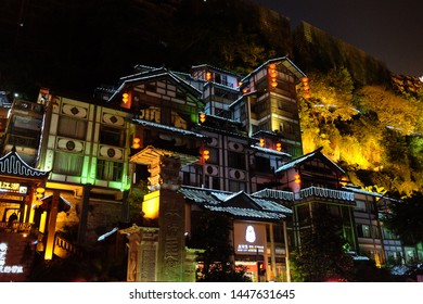 Chongqing/China-May2016: buildings of Hong Ya Dong on the hill in golden lights at night. Famous tourist attraction for its houses similar with scenes of Japanese cartoon Spirited Away