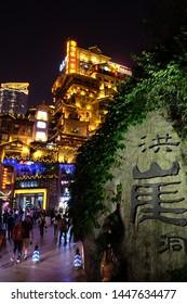 Chongqing/China-May2016: close up stone name sign of Hong Ya Dong at night. Translation is Hong Ya Dong. Famous tourist attraction for its houses similar with scenes of Japanese cartoon Spirited Away