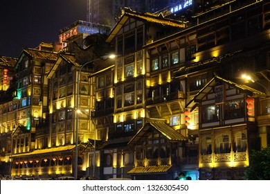 Chongqing/China-May2016: stilted buildings of Hong Ya Dong in golden lights at night. Famous tourist attraction for its houses similar with scenes of Japanese cartoon Spirited Away