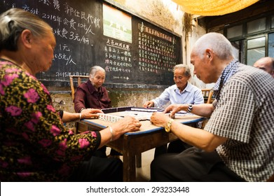 Chongzhou, Sichuan Province, China - May 30, 2015: Old chinese people playing Mahjong in a tearoom.