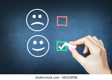 Choose to be happy with tick against smiley face on chalkboard