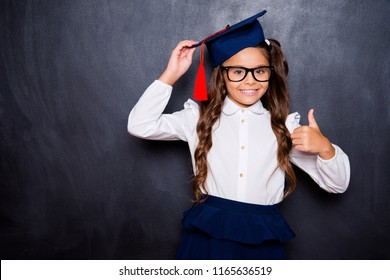 Choose great international education abroad! Positive glad nice adorable cute small little girl with curly ponytail in white shirt, skirt, master's hat, giving thumb-up. Isolated over black background