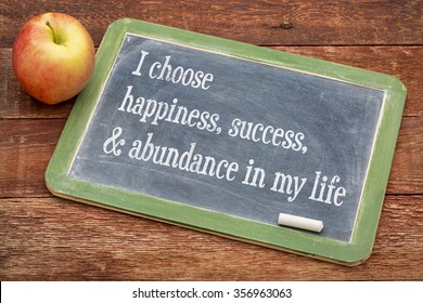 I choose happiness, success and abundance in my life - positive affirmation words on a slate blackboard against red barn wood