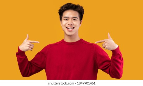 Choose An Pick Me. Self-assured and charismatic asian man pointing at self, wearing red sweater. Egocentric man promoting himself, indicating his body, isolated over orange studio background
