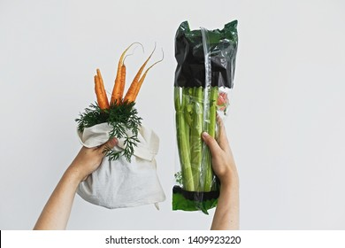 Choose plastic free. Hands holding reusable eco friendly bag with fresh carrots against celery in cellophane plastic package on white background. Zero waste grocery shopping. Ban plastic.