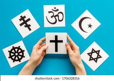 Choose religion concept. Hand with catholic cross near world religions symbols on blue background top view - Shutterstock ID 1706328316