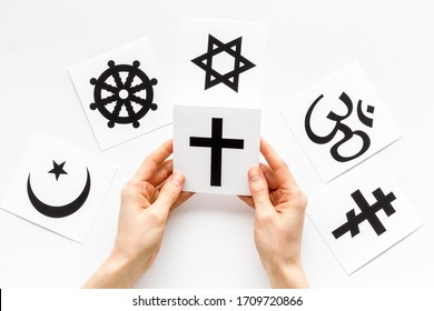 Choose religion concept. Hand with catholic cross near world religions symbols on white background top view - Shutterstock ID 1709720866