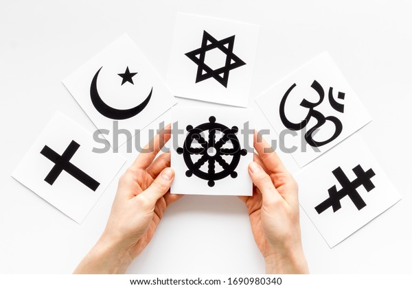 Choose religion concept. Hands with Buddhist wheel near world religions symbols on white background top view