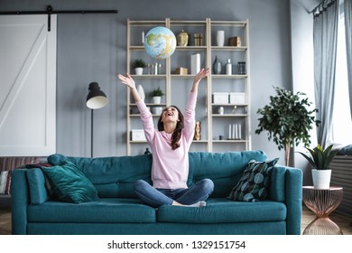 Choose a trip. Happy woman at home on the sofa throws up a globe.