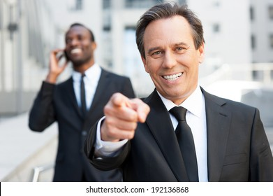 I choose you! Confident senior man in formal wear pointing you and smiling while African man talking on the mobile phone in the background