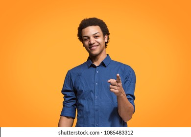 I choose you and order. The smiling business man point you, want you, half length closeup portrait on orange studio background. The human emotions, facial expression concept. Front view. Trendy colors