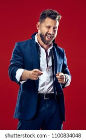 I choose you and order. The smiling business man point you, want you, half length closeup portrait on red studio background. The human emotions, facial expression concept. Front view. Trendy colors