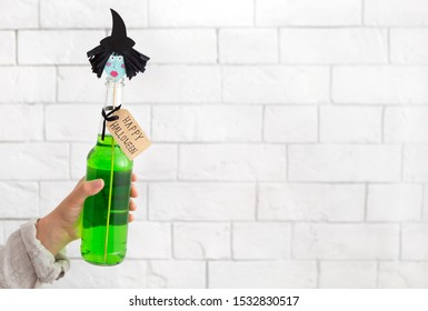 Choose your Halloween witch. Woman holding creative green cocktail with decoration over white bricks wall , copy space