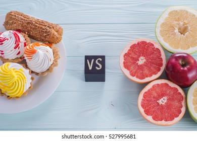 Choosing between Fruits and Sweets. Healthy versus unhealthy food. Weight Loss. Unhealthy tempting cakes and healthy fruits