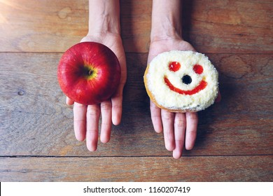 Choosing between red apple and smile face donut, choices between healthy and fat