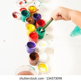 Choosing colors for first drawing - close-up of paint buckets with kids hand and paintbrush