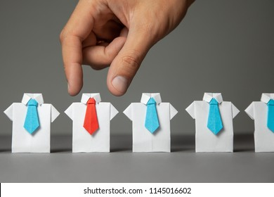 Choosing good employee leader. Man chooses and takes in the hand an employee in shirt and red tie. Staff recruitment.