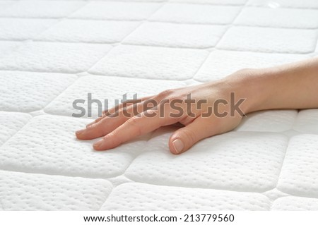 Choosing mattress and bed. Close-up of female hand touching and testing mattress in a store. Copy space.