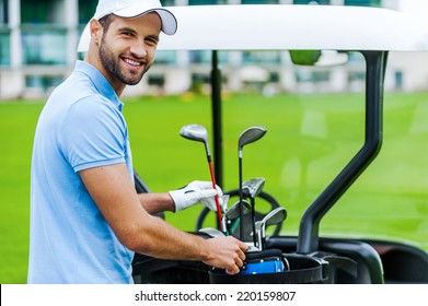 Choosing the proper driver. Handsome young male golfer choosing driver while standing near the golf cart