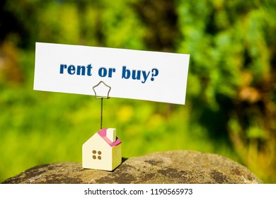 choosing rent or buy option ,small house model isolated on nature background, housing real estate and property owner concept. real estate question, businessman making decision.Country house. Copy