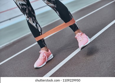 Choosing the right direction. Close up of young woman in sports clothing exercising using resistance band while standing on the running track outdoors