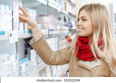 Choosing wisely. Attractive cheerful female taking a product from the store shelf smiling while shopping consumerism shopping choice beauty cosmetics youth store supermarket concept