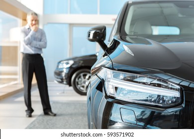 Choosing wisely. Selective focus on a car mature businessman standing thinking choosing a new car at the dealership copyspace choice decision business choosing buying a car consumerism purchase sales