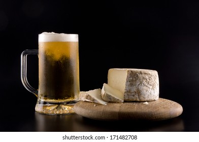 A chop ice cold beer with a wheel of cheese on a wooden board