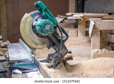 A chop saw sits in a pile of saw dust, in a wood workers work shop