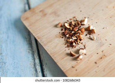 Chopped almonds on a wood cutting board on blue wooden table