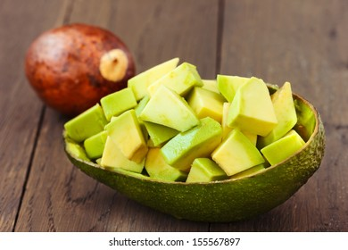 Chopped Avocado fruit with core on brown wooden old table.