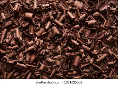 Chopped chocolate background. Flat lay of milk chocolate shavings. Close-up of baking chocolate texture.
