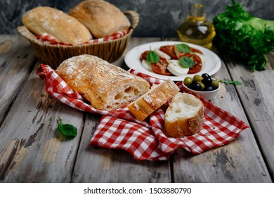 Chopped ciabatta with Caprese, herbs and olives on wooden background