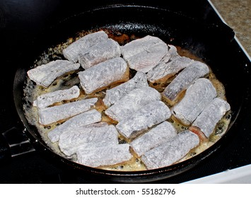 Chopped eels in flour being fried in a pan, a traditional Danish dish, also known as stegte ål