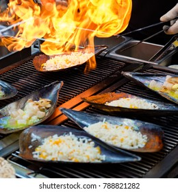 Chopped fresh Atrina pectinata, with cheese on top, are cooked by a flamethrower (Korean street food)