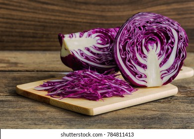 Chopped fresh red cabbage on cutting board to shredded with knife kitchen on wood table with copy space. Prepare sliced vegetable for cooking purple cabbage salad or coleslaw. Homemade food concept.