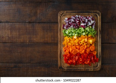 Chopped fresh vegetables arranged on cutting board on dark wooden table with copy space, top view