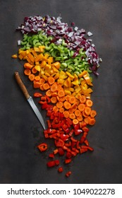 Chopped fresh vegetables with knife on dark background, top view