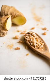 Chopped ginger in wooden spoon against white background.