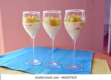 Chopped grapes on top of vanilla pudding / vanilla ice-cream in a wine glass on blue table mat.