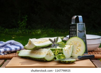 Chopped large spotted zucchini in the garden on the table