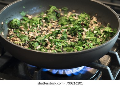 Chopped mushrooms and spinach sauteing in pan on gas burner.