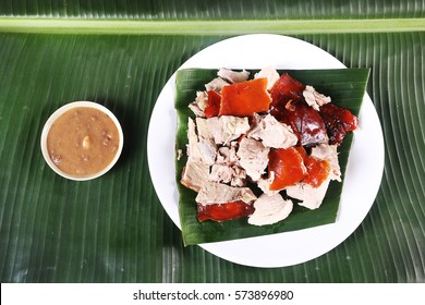 Chopped parts of the delicacy lechon or suckling pig on a banana leaf. The food is popular in Spain and former Spanish colonial regions especially during fiesta
